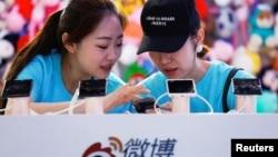 """2018年4月27日,在北京舉行的全國移動互聯網大會(GMIC)期間,工作人員在新浪微博的攤位上使用智能手機。一個人的帽上有英文,意思是""""我是來讓人心碎的""""。"""