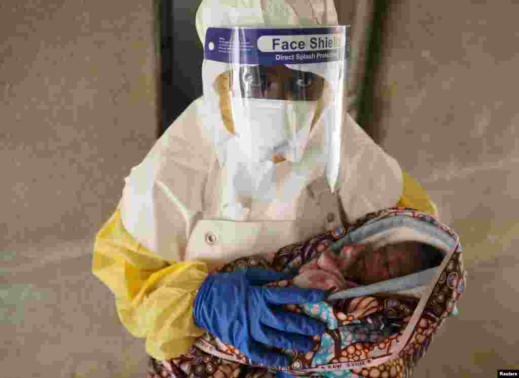A health care worker carries a baby suspected of being infected with Ebola virus in a hospital in Oicha, North Kivu Province of Democratic Republic of Congo.