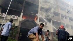 Nhân viên cứu hỏa Ai Cập cố gắng dập tắt ngọn lửa sau khi những người ủng hộ tổng thống bị lật đổ Morsi tràn vào đốt tòa nhà, 15/8/13