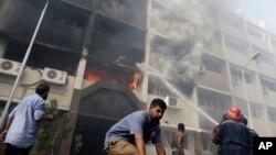 Petugas berusaha memadamkan kebakaran di gedung pemerintahan di Kairo yang diserang dan dibakar oleh para demonstran Mesir yang marah. (AP/Hassan Ammar)