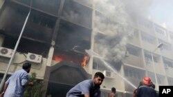 埃及消防队员8月15日在吉萨被抗议人士点燃的政府大楼前救火。