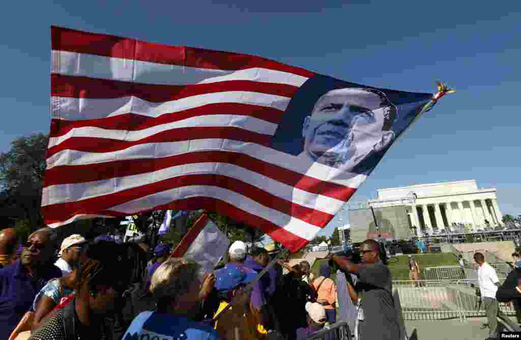 A marcher holds an U.S. flag bearing the image of President Barack Obama during the 50th anniversary of the 1963 March on Washington for Jobs and Freedom at the Lincoln Memorial in Washington Aug. 24, 2013.