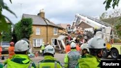 Para petugas tengah menyingkirkan pohon yang rubuh di Jalan Bath di Hounslow, London barat (28/10).