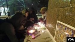 活动参加者在甘地像下点燃蜡烛。(美国之音白桦拍摄)