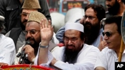 Pakistan's Hafiz Saeed, leader of a Pakistani religious group, center, waves during an anti-Indian rally in Lahore, July 19, 2016.