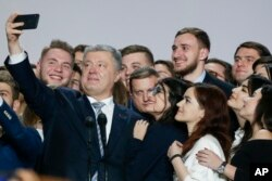 FILE - Ukrainian President Petro Poroshenko takes a selfie with supporters in Kyiv, Ukraine, Jan. 29, 2019.
