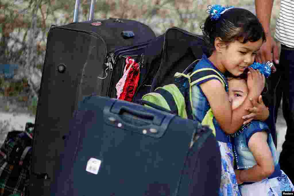 A girl hugs her sister before they leave the Palestinian Rafah border crossing with Egypt, which was reopened for the first time since March due to concerns about the spread of the coronavirus, in the southern Gaza Strip.