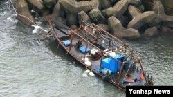 24일 일본 아키타현 유리혼조시 해안의 방파제에 목조 어선이 표류해 있다. 일본 언론은 전날 이 배와 북한 국적 추정 남성 8명이 발견돼 경찰이 조사 중이라고 보도했다.