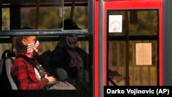 People wearing a face mask sit in a bus in Belgrade, Serbia, Friday, May 8, 2020. (AP Photo/Darko Vojinovic)
