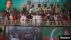 Supporters of Imran Khan (on screens top and R), chairman of the opposition Pakistan Tehreek-e-Insaf (PTI) political party, chant anti-government slogans during his speech at a rally in Karachi September 21, 2014. Protesters led by Imran Khan, a former cricket star, and Tahir ul-Qadri, a firebrand cleric, have been locked in a bitter stand-off with the government since mid-August. (REUTERS/Akhtar Soomro)