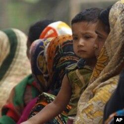 A woman waits in line to buy subsidized rice in Bangladesh.