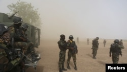 FILE - Cameroonian soldiers from the Rapid Intervention Brigade stand guard amidst dust kicked up by a helicopter in Kolofata, Cameroon, March 16, 2016.