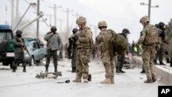 Polisi Afghanistan dan pasukan NATO memeriksa jalan raya antara Jalalabad-Kabul, Afghanistan menyusul insiden ledakan bom bunuh diri dengan menggunakan mobil, yang menewaskan tiga tentara NATO (27/12).