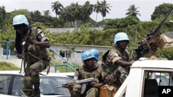 A U.N. soldier jumps out of a pickup truck after security forces loyal to strongman Laurent Gbagbo fired to disperse women protesting for a peaceful solution to the nation's political crisis near the U.N. compound in Abidjan, Mar 3 2011