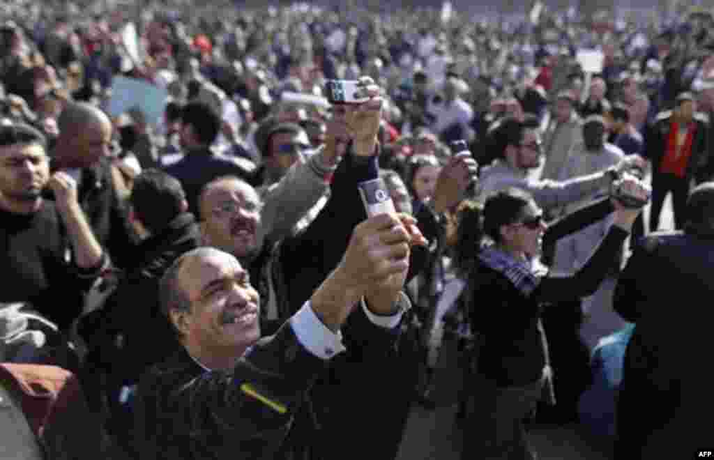 Egyptian anti-government protesters take photos of one of the many and colorful placards with their camera phones at the continuing demonstration in Tahrir square in downtown Cairo, Egypt, Monday, Jan. 31, 2011. A coalition of opposition groups called for