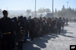 FILE - Migrants and refugees wait in a queue to be allowed to pass from the northern Greek village of Idomeni to southern Macedonia, Nov. 9, 2015.