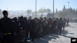 Migrants and refugees wait in a queue to be allowed to pass from the northern Greek village of Idomeni to southern Macedonia, Nov. 9, 2015.