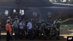 ທະຫານອີນໂດເນເຊຍ ຫາມສົບຜູ້ເຄາະຮ້າຍ ຈາກເຮືອບິນຕົກໃນວັນພຸດທີ່ Cijeruk ໃນ Bogor, ເຂດ Java ຕາເວນຕົກ, ອີນໂດເນເຊຍ, ວັນເສົາ, ທີ່ 12, ເດືອນພຶດສະພາ 2012.