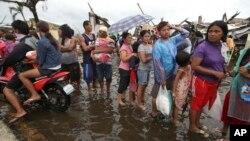 Những người sống sót xếp hàng chờ lãnh phẩm vật cứu trợ trên một con đường bị ngập nước tại thành phố Tacloban bị bão tàn phá, miền trung Philippines, ngày 12/11/2013.