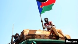 A man waves a South Sudanese flag as he celebrates referendum results in the town of Abyei, Oct. 31, 2013.