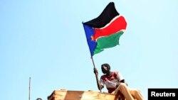 Seorang pria melambaikan bendera Sudan Selatan saat ia merayakan hasil referendum di kota Abyei, Oktober 2013. (Reuters/Goran Tomasevic)