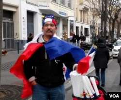 Moroccan Mustapha el-adkour selling flags near Place de la Republique, Jan. 10, 2016. (Lisa Bryant/VOA)