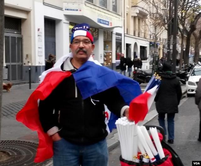 Moroccan Mustapha el-adkour selling flags near Place de la Republique, Jan. 10, 2016. (Lisa Bryant/VOA)