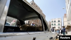 People gather near a car damaged by a mortar shell during fighting between Shi'ite Houthi militants and government forces in Sanaa September 19, 2014.