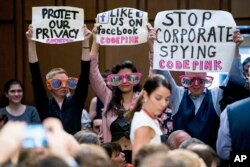 "Members of the audience hold up signs and wear sunglasses that read ""Stop Spying"" before CEO Mark Zuckerberg arrives to testify before a joint hearing of two Senate committees on Capitol Hill in Washington, April 10, 2018, about the use of Facebook data t"