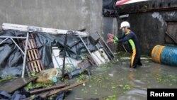 Seorang warga Wujie di Ilan County, Taiwan, berupaya membersihkan puing-puing yang berserakan di dekat rumahnya yang dilanda banjir. Topan Saola disertai hujan lebat menimbulkan tanah longsor dan melumpuhkan hampir seluruh Taiwan (2/8).