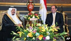 In this picture provided by the office of the Egyptian Presidency, Egyptian President Abdel-Fattah el-Sissi, right, sits with Saudi Arabia's King Salman in the Abdeen Palace, Cairo, April 9, 2016.