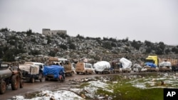 Syrian civilians flee from Idlib in rain toward the north to find safety inside Syria near the border with Turkey, Feb. 13, 2020.