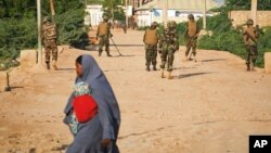 FILE - A Somali woman crosses a street while soldiers with the African Union Mission in Somalia (AMISOM) stand guard 300 kilometers west of the capital Mogadishu, on a street in Belet Weyne, Somalia.
