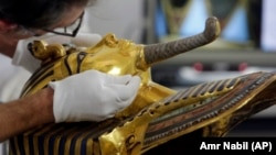 German restorer Christian Eckmann begins restoration work on the golden mask of King Tutankhamun over a year after the beard was accidentally broken off and hastily glued back with epoxy, at the Egyptian Museum in Cairo, Egypt, Tuesday, Oct. 20, 2015. The