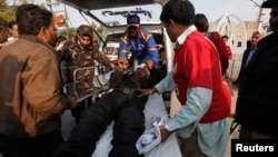 After a deadly bomb blast on a bus, rescue workers move an injured policeman on a stretcher, outside Jinnah Postgraduate Medical Centre Hospital in Karachi, Feb. 13, 2014.