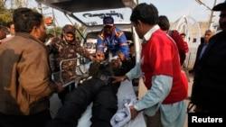 "Petugas membawa seorang polisi yang terluka akibat serangan bom di sebuah bus ke rumah sakit ""Jinnah Postgraduate Medical Centre"" di Karachi (13/2)."