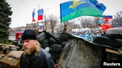 Pro-Russian supporters and an Orthodox priest (front) stand next to a barricade in front of the seized office of the SBU state security service in Luhansk, in eastern Ukraine on April 11, 2014.