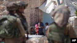 Tentara Israel berjaga-jaga dekat sebuah keluarga Palestina di luar rumah mereka dalam pencarian terhadap tiga remaja yang diculik di Hebron, Tepi Barat (18/6). (AP/Majdi Mohammed)