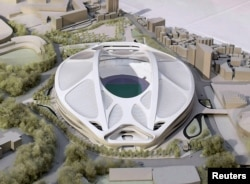 FILE - A rendering model of the new National Stadium for 2020 Tokyo Olympics and Paralympics, designed by Iraqi-British architect Zaha Hadid, is displayed at a meeting of members of the advisory council on the construction of the new stadium in Tokyo.