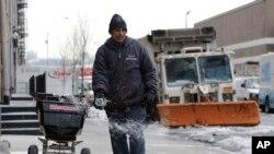 26일 미국 뉴욕시에서 폭설에 대비하여 보도에 제설제를 뿌리고 있다.