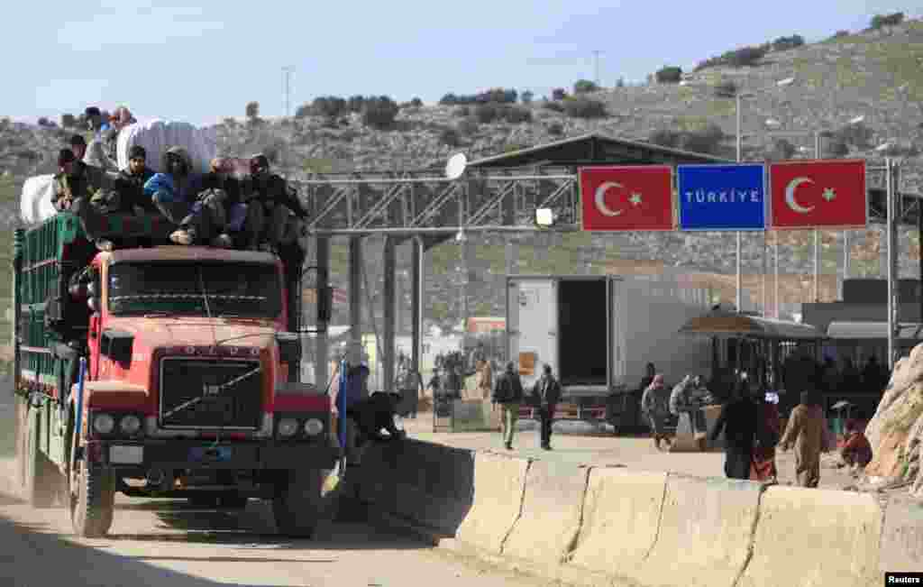 People sit on the top of a truck at the Syrian border crossing of Bab al-Hawa, at the Syrian-Turkish, Feb. 6, 2014.