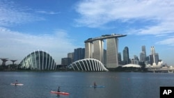 Kayaks are dwarfed against the skyline of the Marina Bay, which is home to popular hotels, and tourist attractions, March 21, 2017, in Singapore.