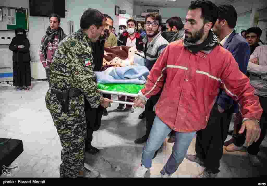 Des secouristes transportent une victime vers un hôpital, dans l'ouest de l'Iran, le 13 novembre 2017.