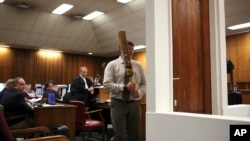Forensic investigator Johannes Vermeulen, with a cricket bat in hand, demonstrates on a mock-up toilet and door details of how the door could have been broken down, during the trial of Oscar Pistorius in Pretoria, South Africa, March 12, 2014.