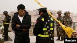 지난해 중국 서부의 신장 자치구에서 경찰이 위구르족 남성의 신원을 확인하고 있다.