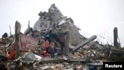 이스라엘군과 하마스의 교전으로 파괴된 주택가 폐허에서 , 4일 한 팔레스타인 어린이가 비를 피하고 있다.