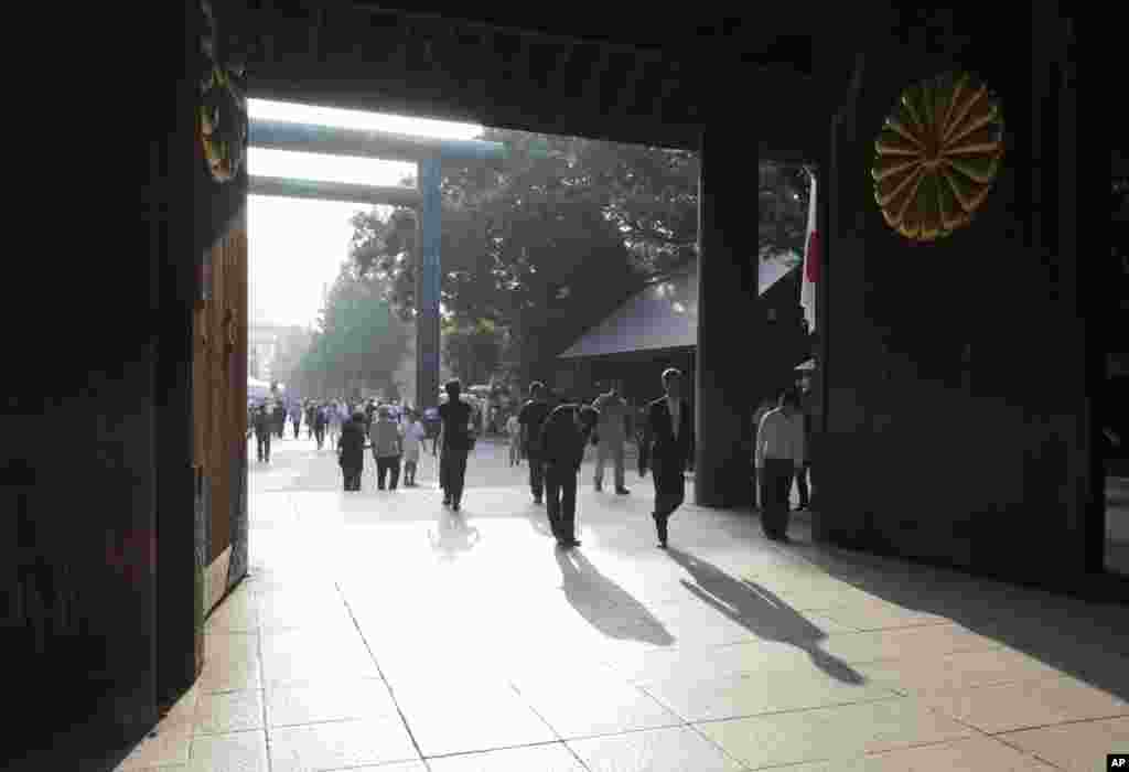 People bow at the Yasukuni Shrine in Tokyo, August 15, 2013.