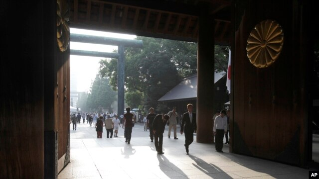 People bow at the Yasukuni Shrine in Tokyo, Aug. 15, 2013.