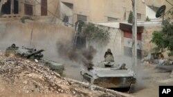 ລົດລຳລຽງພົນຄັນນຶ່ງຂອງຊີເຣຍ ຖືກຕິດຕາມດ້ວຍລົດຖັງ ທີ່ເມືອງ Harasta ທາງຕາເວັນອອກສຽງເໜືອ ຂອງນະຄອນ Damascus ປະເທດຊີເຣຍ ວັນທີ 22 ຕຸລາ 2015.