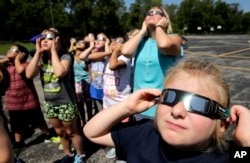 Fourth graders at Clardy Elementary School in Kansas City, Missouri, practice the proper use of their eclipse glasses in anticipation of Monday's solar eclipse, Aug. 18, 2017.